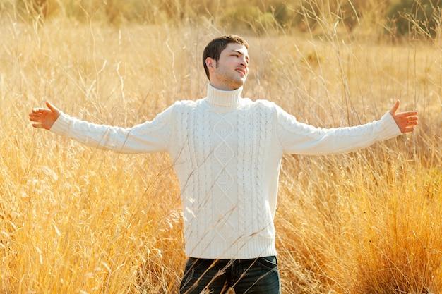 Homem de outono no campo dourado com camisola de gola alta
