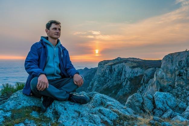 Homem de paletó azul sentado em uma rocha
