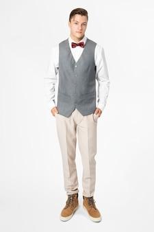 Homem de paletó cinza e gravata-borboleta, traje formal masculino de corpo inteiro