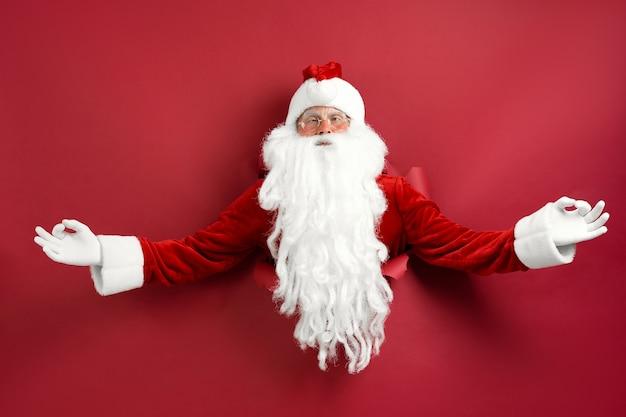 Homem de papai noel meditando através do buraco no papel. desconto. vendas de natal. decorações de natal. espaço para texto.