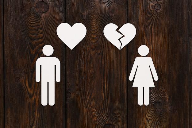 Homem de papel com coração e mulher com coração partido na madeira