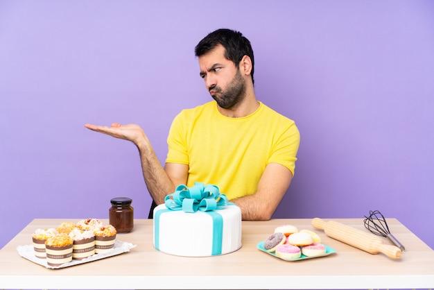Homem de pastelaria com mesa cheia de doces