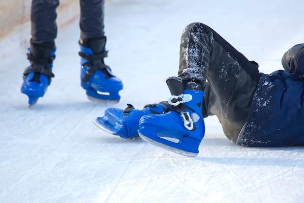 Homem de patins azuis caiu no gelo. pessoas patinando no gelo em uma pista de gelo. hobbies e esportes. férias e atividades de inverno.