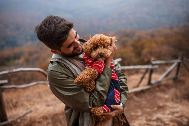 Homem de pé ao ar livre e segurando o cachorro