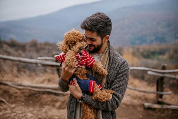 Homem de pé ao ar livre e segurando o cão.