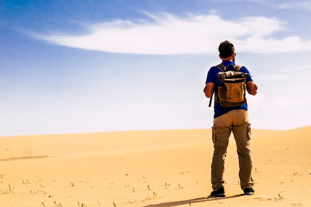 Homem de pé atrás com uma mochila olhando as dunas do deserto de areia e o céu azul