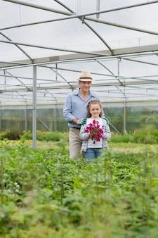 Homem de pé com neta segurando flores roxas