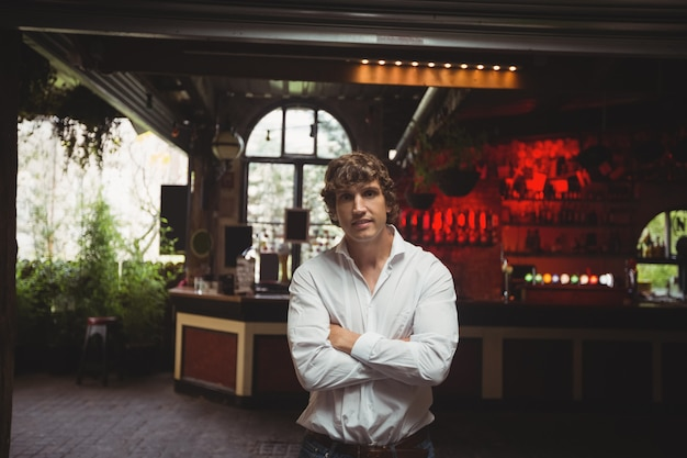 Homem de pé com os braços cruzados no bar
