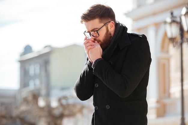 Homem de pé e curvando-se nas mãos ao ar livre em tempo frio