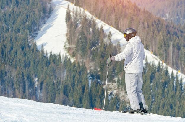 Homem de pé em esquis em uma ladeira nevada