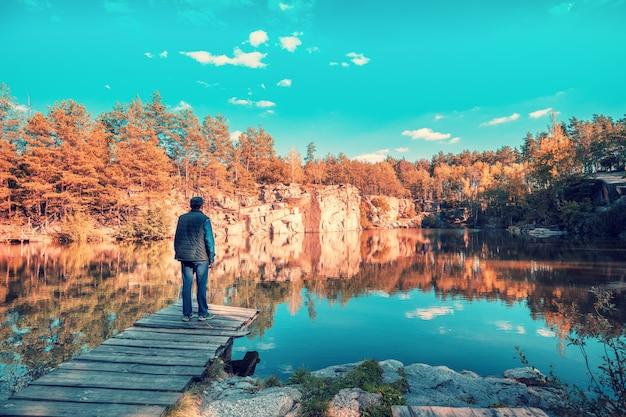 Homem de pé em um deck de madeira olhando para o lago com margem de granito
