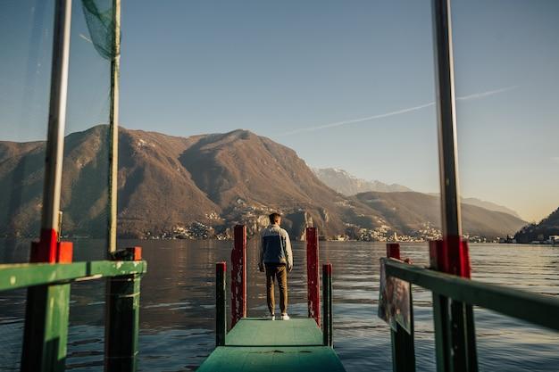 Homem de pé em um píer no lago lugano, na suíça.
