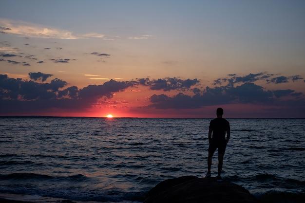 Homem de pé em uma pedra à beira-mar e assistindo o nascer do sol