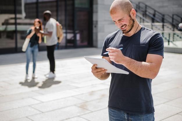 Homem de pé fora mantendo o bloco de notas sorrindo