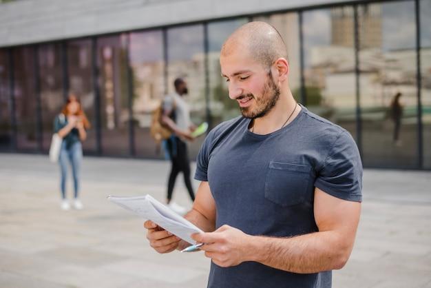 Homem de pé fora segurando bloco de notas e caneta