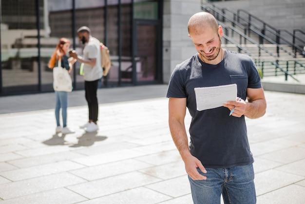 Homem de pé fora segurando bloco de notas sorrindo