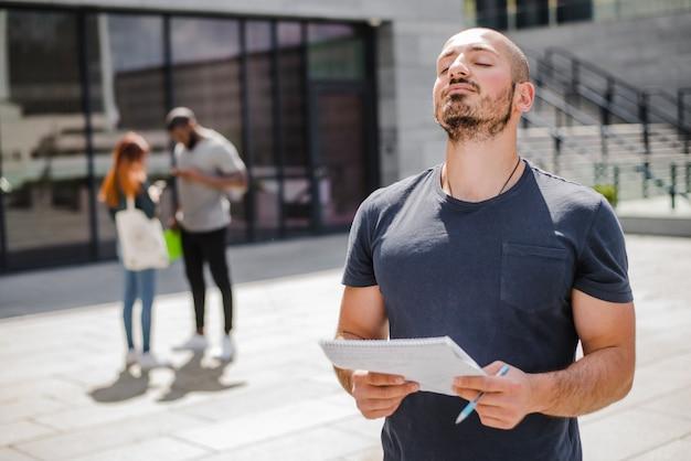 Homem de pé fora segurando notepad meditando
