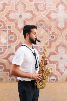 Homem de pé lateralmente tocando saxofone com fundo geométrico