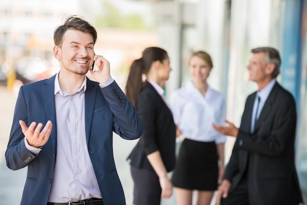 Homem de pé na frente do escritório e falando no telefone.