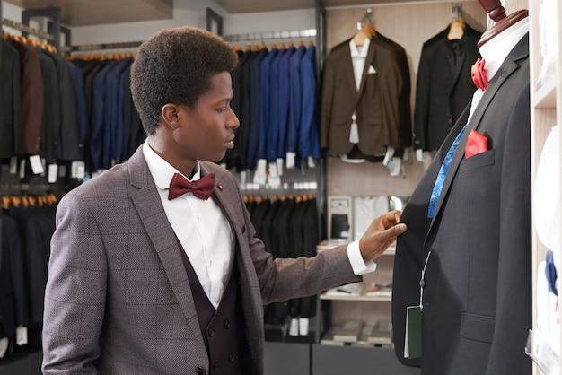 Homem de pé na loja com roupas perto de manequim.