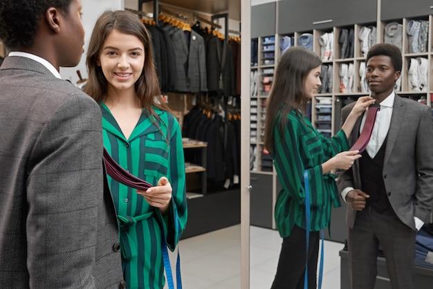 Homem de pé na loja, olhando no espelho, escolhendo a gravata.
