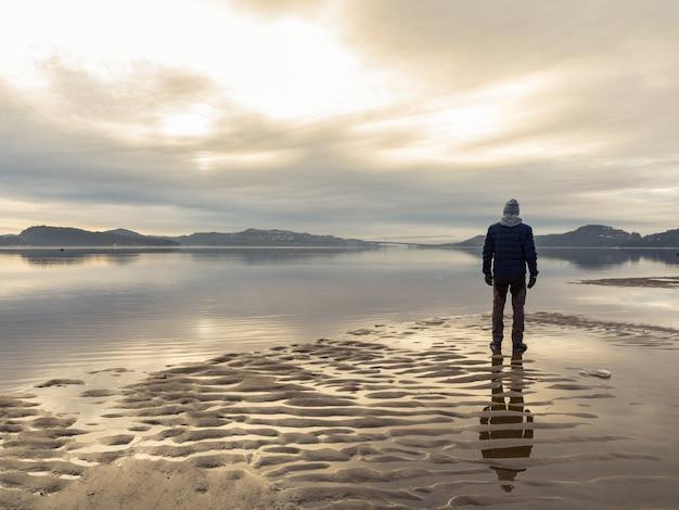 Homem de pé na praia, reflexões do homem na água. mar calmo, névoa e nevoeiro. hamresanden, kristiansand, noruega