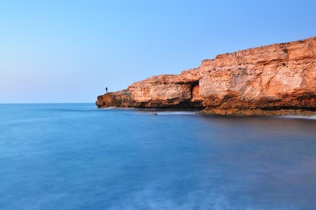 Homem de pé na rocha ao longo da costa do mar negro, com águas azuis claras e a paisagem de céu azul na crimeia.
