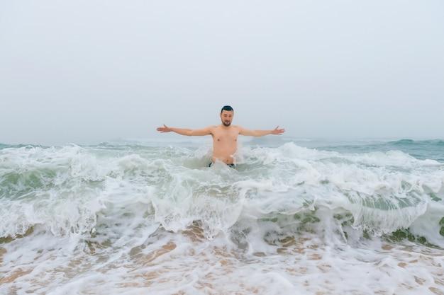 Homem de pé nas ondas com as mãos afastadas