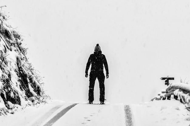 Homem de pé no chão coberto de neve branca ao lado da montanha