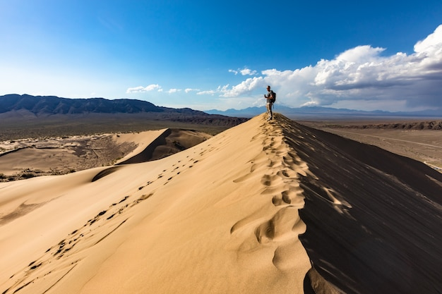 Homem de pé no topo da duna de areia