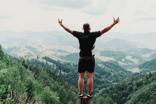 Homem de pé no tronco nas montanhas de verão ao pôr do sol e apreciando a vista da natureza