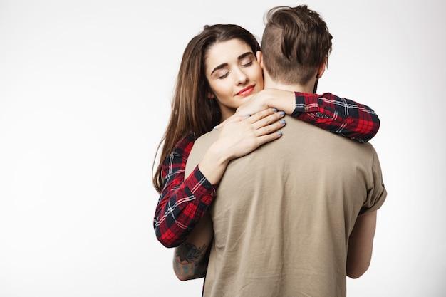 Homem de pé para trás, namorada, abraçando-o romanticamente