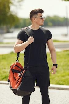 Homem de pé perto da água. cara com uma roupa esportiva. macho em um parque de verão com mochila