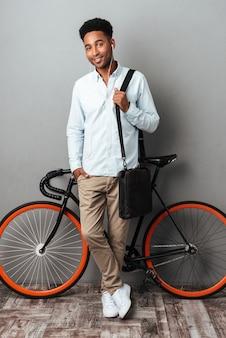 Homem de pé perto da bicicleta isolada sobre fundo cinza