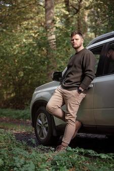 Homem de pé perto do carro na floresta no espaço da cópia da estrada da trilha. estação do outono
