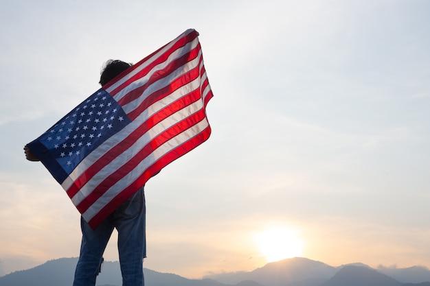 Homem de pé segurando a bandeira dos eua na vista do nascer do sol