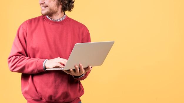 Homem de pé usando laptop
