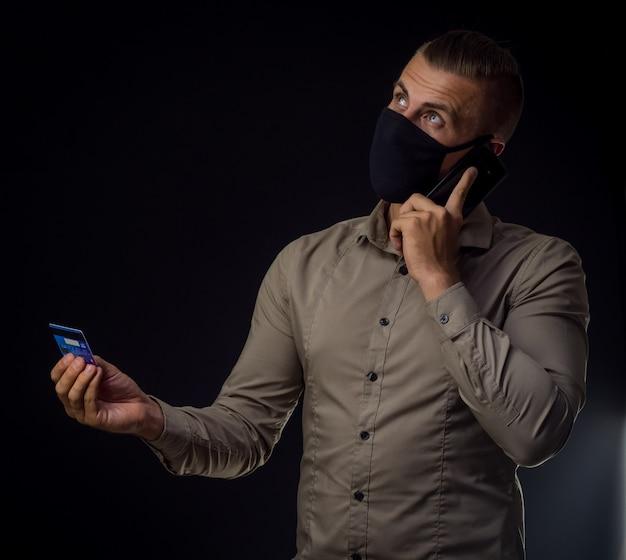 Homem de pedidos on-line com cartão de crédito e telefone sobre parede preta