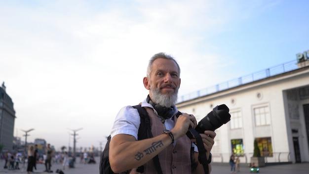 Homem de pele clara olha confiante para a frente e sorri na praça da cidade