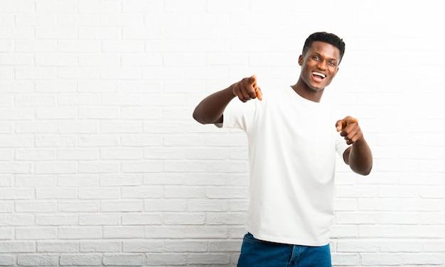 Homem de pele escura aponta o dedo para você enquanto sorrindo