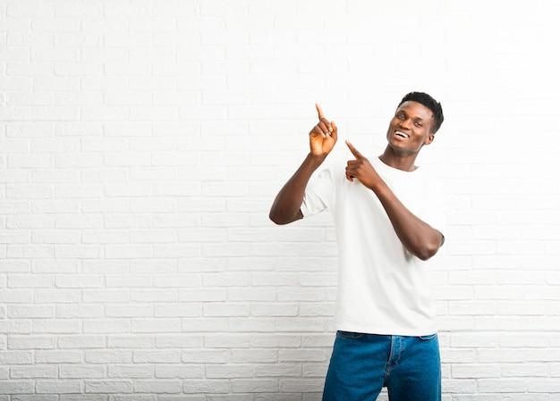 Homem de pele escura, apontando com o dedo indicador uma ótima idéia e olhando para cima