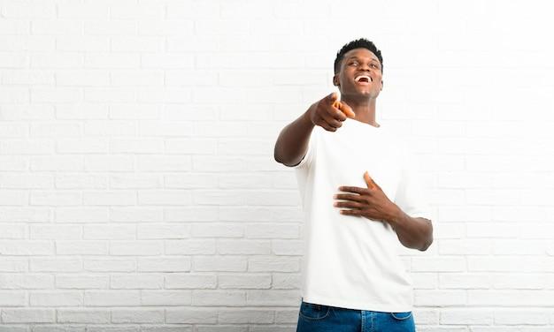Homem de pele escura apontando com o dedo para alguém e rindo muito