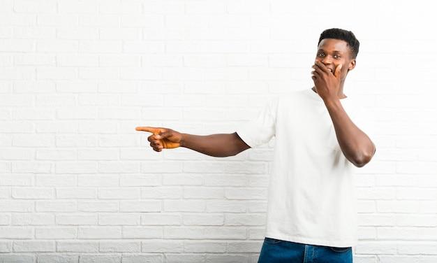 Homem de pele escura, apontando o dedo para o lado e apresentando um produto com uma cara de surpresa