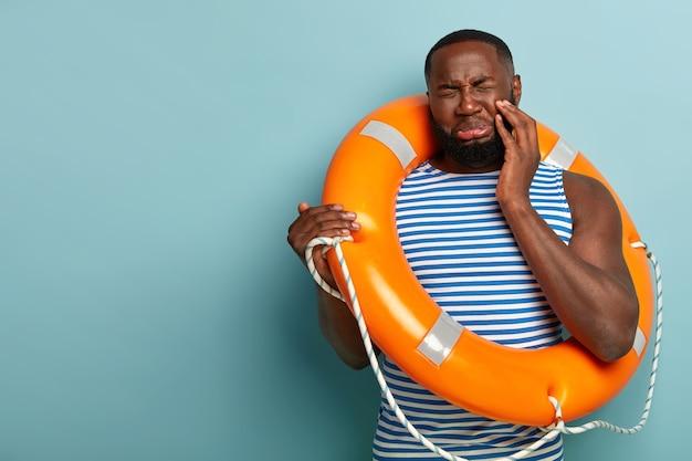Homem de pele escura, barba por fazer, triste, com expressão facial triste, fecha os olhos e carrega uma bóia salva-vidas para nadar em segurança