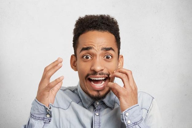 Homem de pele escura chocado com medo gesticula de ansiedade, parece com a boca bem aberta e olhos esbugalhados,