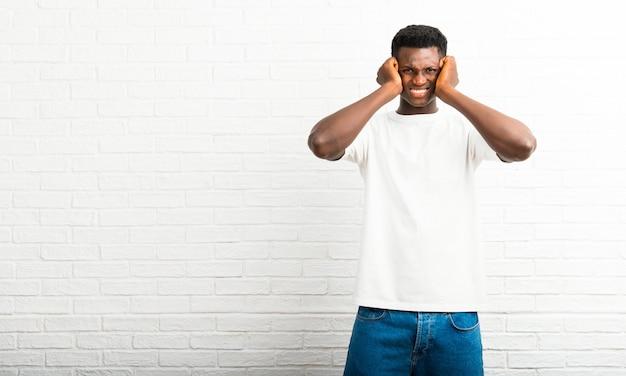 Homem de pele escura cobrindo ambas as orelhas com as mãos. expressão frustrada