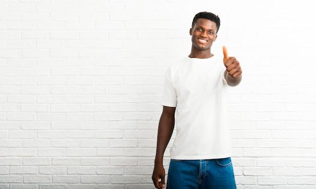 Homem de pele escura dando um polegar para cima gesto e sorrindo porque algo bom aconteceu