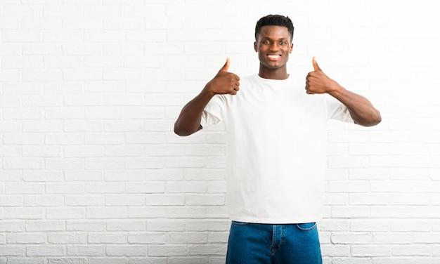 Homem de pele escura dando um polegar para cima gesto e sorrindo porque teve sucesso
