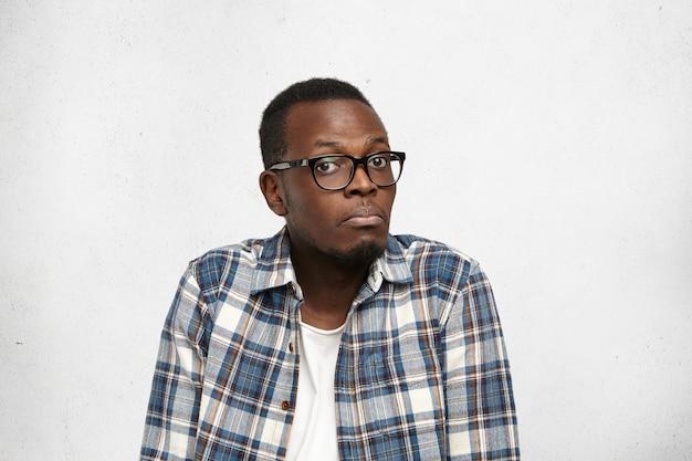 Homem de pele escura de óculos sentado e dando de ombros