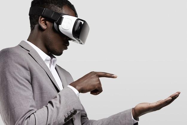 Homem de pele escura em traje formal com fone de ouvido de realidade virtual para smartphone na cabeça, jogando videogame.